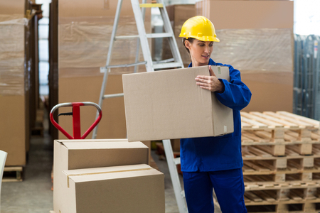 unloading: Delivery worker unloading cardboard boxes from pallet jack in warehouse