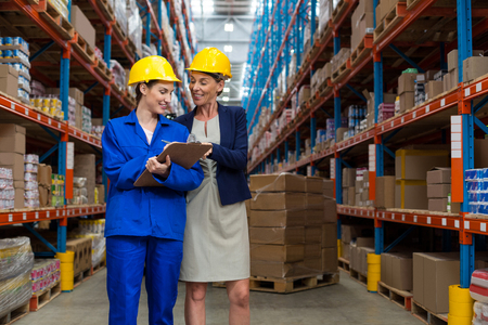 Warehouse manager and worker discussing with clipboard in warehouse
