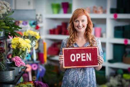 florists: Portrait of smiling florists holding open sign placard in flower shop
