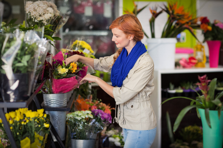 Happy female florist arranging flower bouquet in flower shop