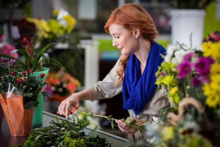 Female florist trimming flower stem at flower shop Stock Photo