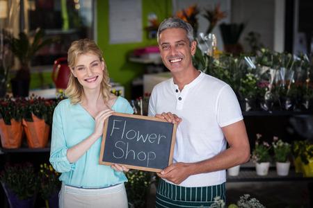 florists: Portrait of smiling florists holding flower shop sign on slate in flower shop Stock Photo