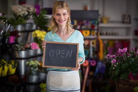 Portrait of smiling female florist holding open sign on slate in flower shop