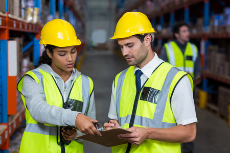 Warehouse workers interacting with each other in warehouse Stockfoto