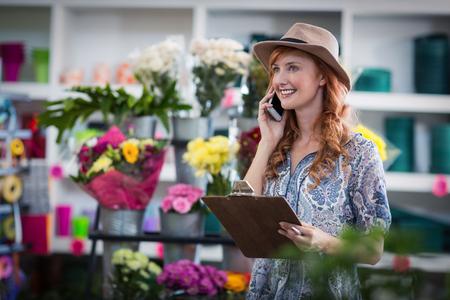 Smiling female florist taking order on mobile phone at flower shop