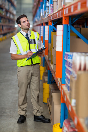 Warehouse manager looking at packages in warehouse