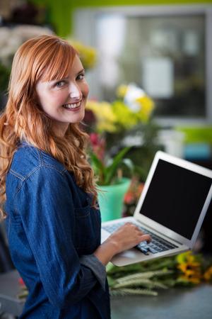 Portrait of smiling florist using laptop in flower shop