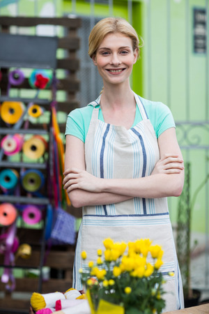 Portrait of happy florist standing with arms crossed in flower shop Stock Photo