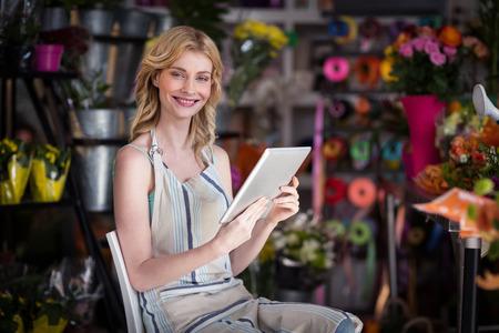 Portrait of smiling female florist using digital tablet in florist shop Stock Photo