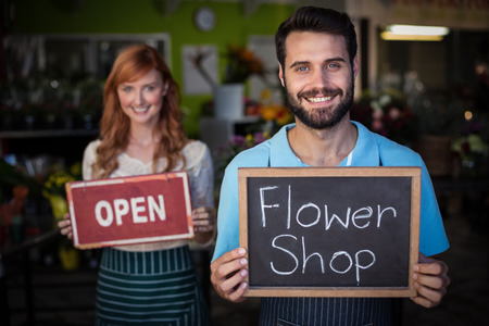 Man holding slate with flower shop sign and woman holding open signboard