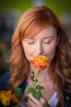 Female florist smelling a rose flower in the shop