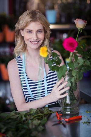 Portrait of smiling female florist arranging flower bouquet in vase at flower shop