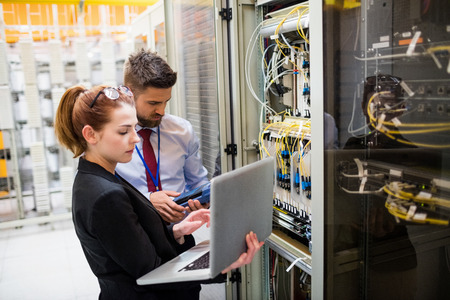 Les techniciens utilisant un ordinateur portable tout en analysant le serveur dans la salle du serveur Banque d'images - 64439729