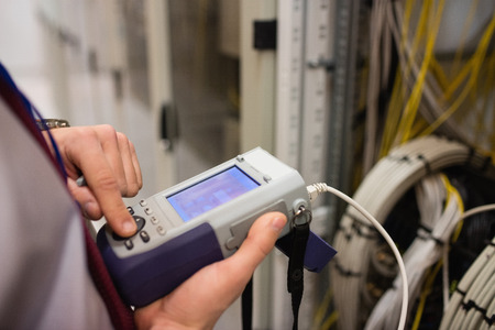 analyzer: Mid section of technician using digital cable analyzer in server room
