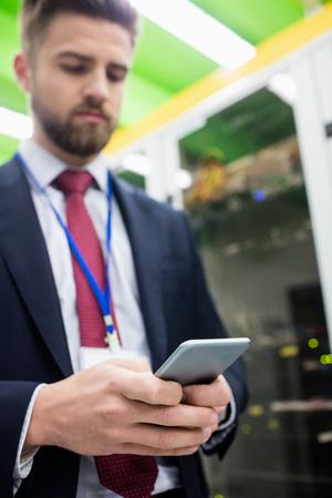 Technician using mobile phone in server room