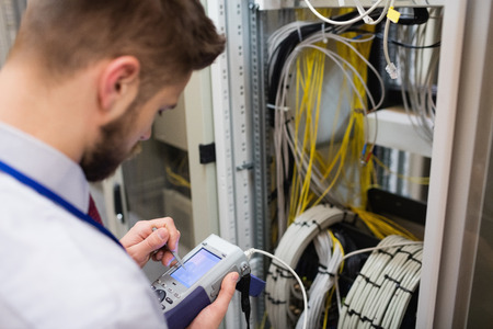 Technician using digital cable analyzer in server room Stock Photo