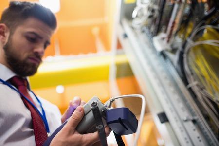 analyzer: Technician using digital cable analyzer in server room Stock Photo