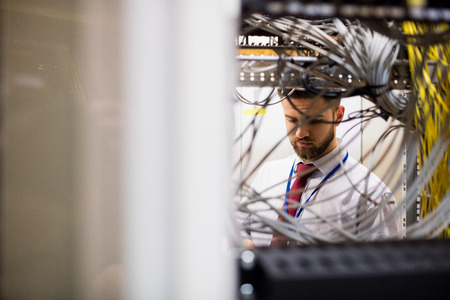 Technician checking cables in a rack mounted server in server room Stock Photo
