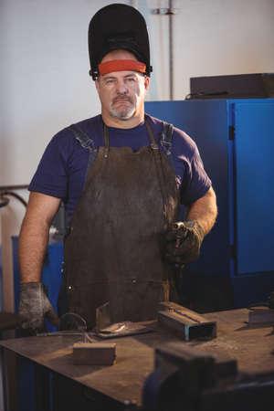 welding machine: Portrait of welder standing with welding machine in workshop