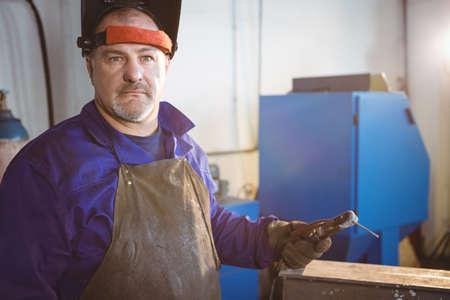 welding machine: Welder standing with welding machine in workshop