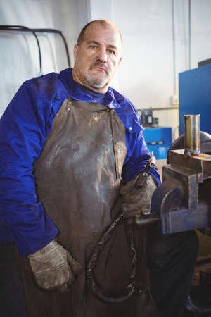 welding machine: Portrait of welder holding welding machine in workshop LANG_EVOIMAGES