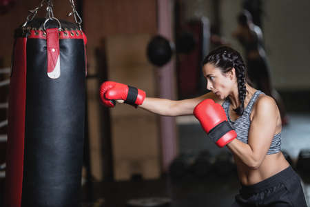 strong toughness: Female boxer practicing boxing with punching bag in fitness studio LANG_EVOIMAGES