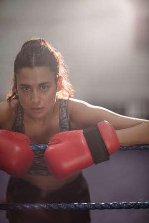 female boxer: Portrait of female boxer in boxing gloves at fitness studio LANG_EVOIMAGES