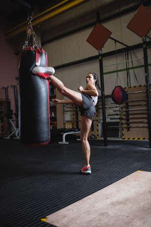 female boxer: Female boxer kicking punching bag in fitness studio