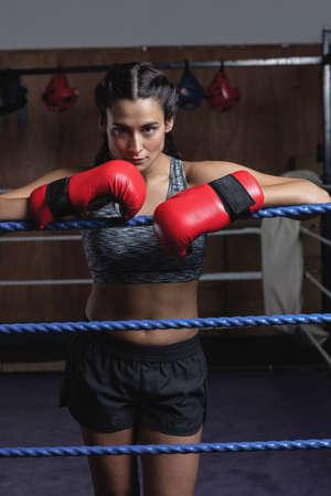 female boxer: Tired female boxer in boxing gloves at fitness studio LANG_EVOIMAGES