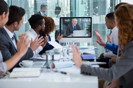 Business people looking at a screen during a video conference in the office