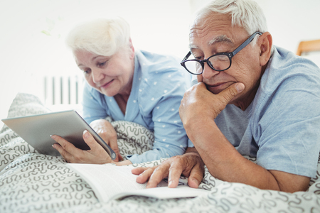 Senior couple reading a book and using digital tablet on bed at bedroom Stock Photo