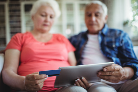 ageing process: Senior couple doing online shopping on digital tablet at home