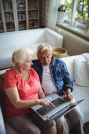 ageing process: Senior couple using laptop at home