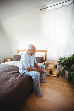 ageing process: Thoughtful senior man sitting on bed at bedroom