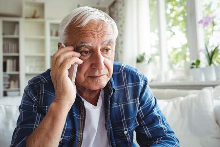 ageing process: Tensed senior man talking on mobile phone at home