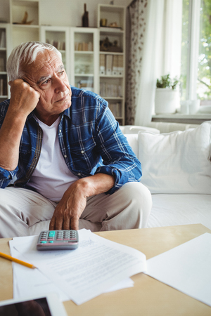 ageing process: Worried senior man sitting on a sofa at home