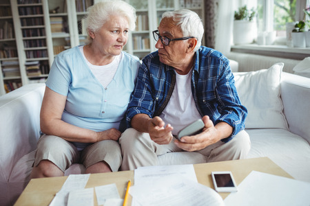 checking account: Worried senior couple interacting while checking the bills at home