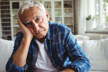 ageing process: Portrait of worried senior man sitting on a sofa at home