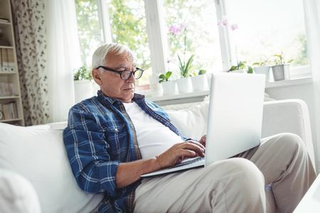 ageing process: Senior man using laptop at home