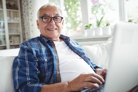 家でノート パソコンを使用して年配の男性の肖像画