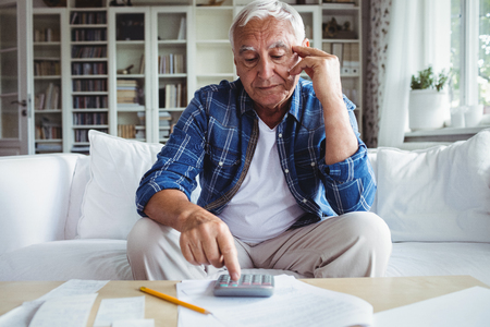 Tensed senior man checking the bills at home Stock Photo