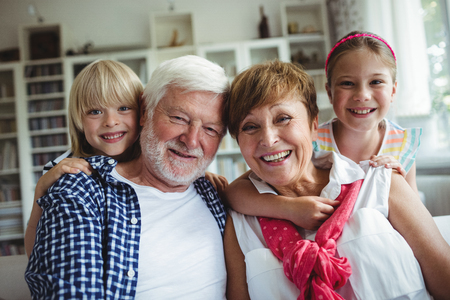 ageing process: Portrait of grandparents smiling with their grandchildren at home
