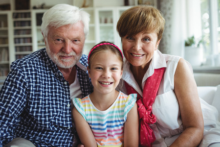 the grand daughter: Portrait of smiling grandparents with her grand daughter at home