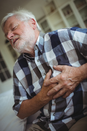 ageing process: Senior man suffering from chest pain at home