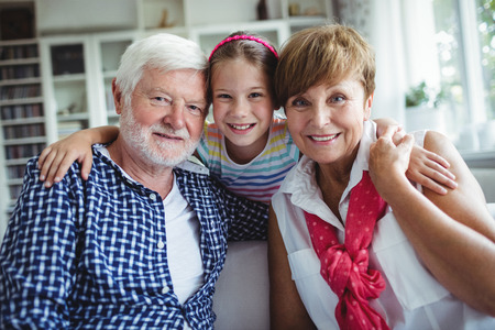grand daughter: Portrait of smiling grandparents with her grand daughter at home