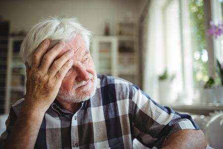 ageing process: Tensed senior man looking away at home
