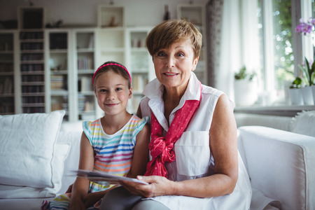 Portrait of senior woman and her granddaughter holding a photo album at home Stockfoto