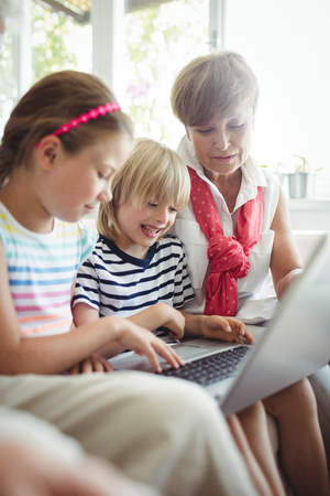 Grandchildren using laptop with their grandmother at home Stock Photo