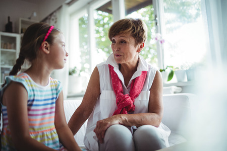 Senior woman and her granddaughter interacting with each other at home Stock Photo