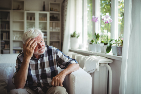 tensed: Tensed senior man sitting on sofa at home